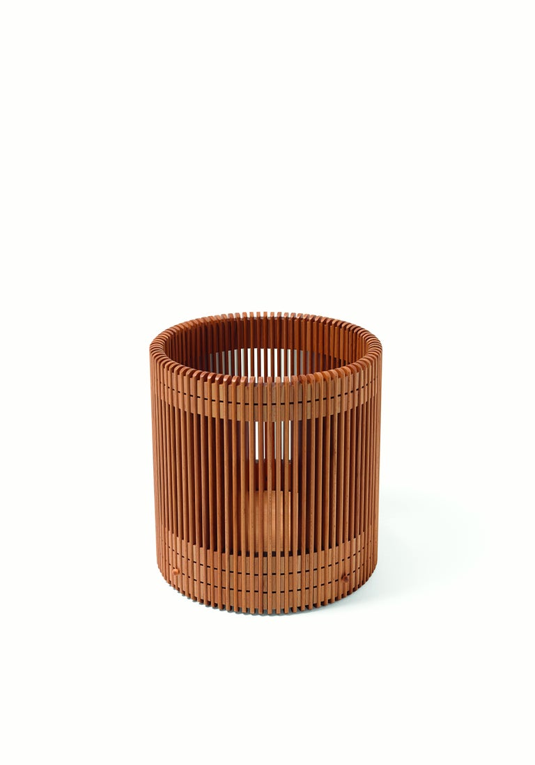 A wastepaper basket made of 89 beechwood baguettes connected by 178 spacers. The vertical elements, individually polished to obtain a total flattening of any edges, are connected by four circles. The bottom is fixed through brass pivots, whose