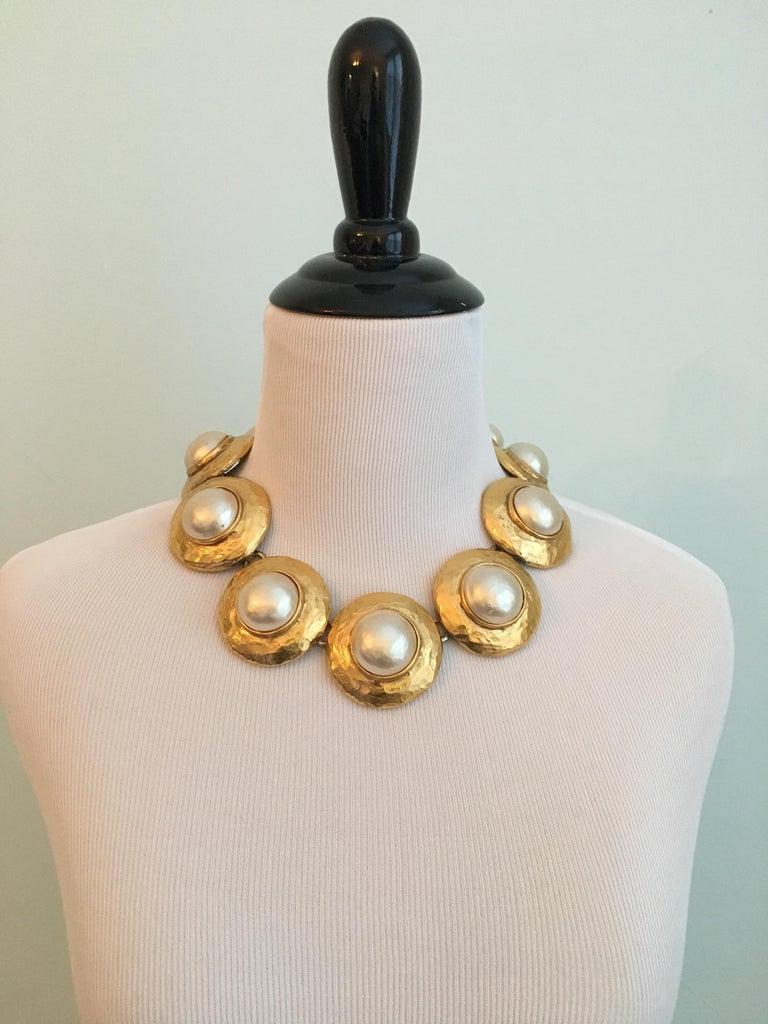 Striking 1980s Yves Saint Laurent necklace made up of large gold plated disks with faux pearl centers made by Goossens. The faux pearls are coated in a thick pearl nacre which give them a beautiful luminous quality. The necklace is adjustable and