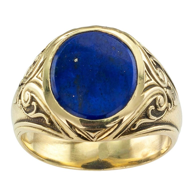 Larter & Sons Art Nouveau lapis lazuli and gold gentleman's ring circa 1905. Centering a bezel-set, buff-top lapis lazuli displaying beautiful blue color with small pyrite markings, between shoulders decorated with classical scrolling motifs, in
