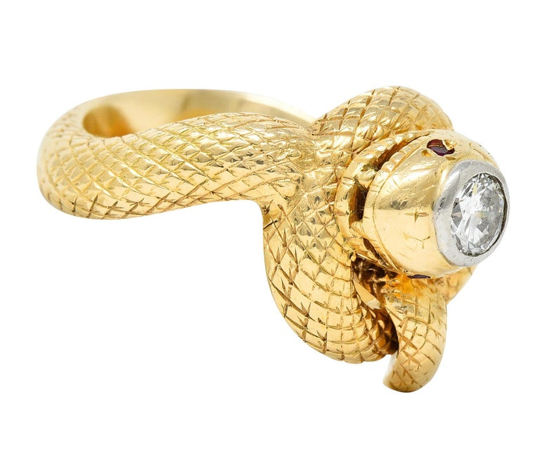 Ring is designed as a coiling snake accented by ruby accent eyes  Deeply engraved throughout with a scale patterning  Featuring a round brilliant cut diamond at its head - bezel set in white gold  Weighing approximately 0.50 carat - J color with SI1