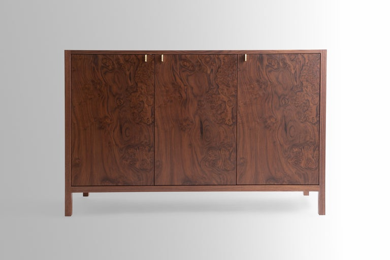 The Laska credenza is built in our Louisville studio using premium hardwoods and thoughtfully selected wood veneers. This piece features custom veneered panels framed flush with solid hardwood edges and legs. The three doors showcase crotch-cut