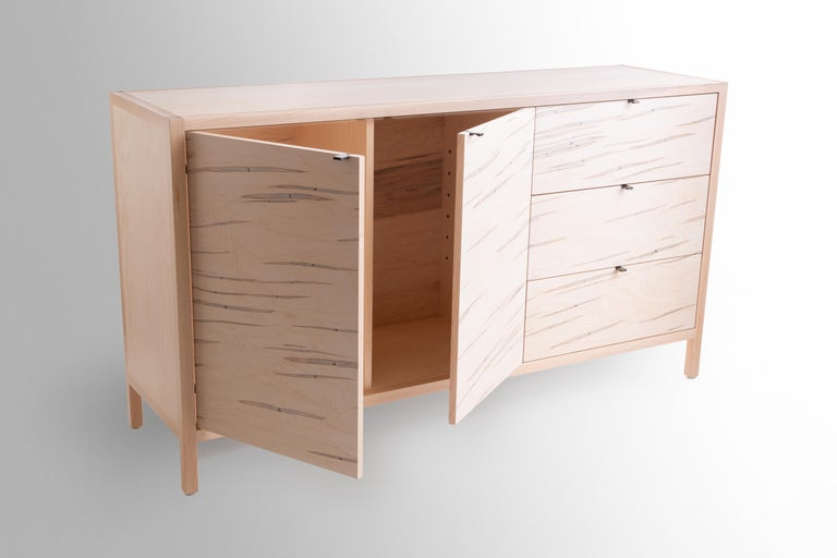 The Laska credenza is built in our Louisville, KY studio using premium hardwoods and thoughtfully selected wood veneers. This piece features custom veneered panels framed flush with solid hardwood edges and legs. The three solid wood drawers ride on
