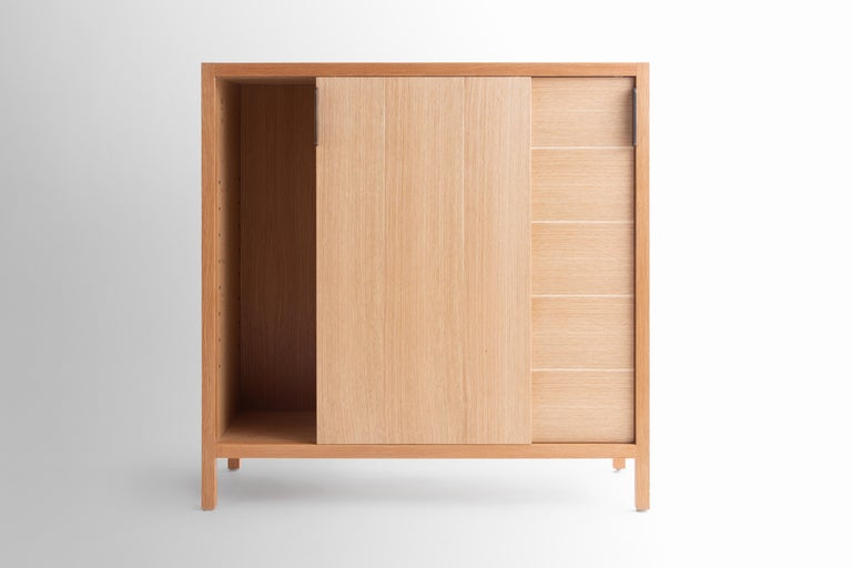 The Laska credenza is built in our Brooklyn studio using premium hardwoods and thoughtfully selected wood veneers. This piece features custom veneered panels framed flush with solid hardwood edges and legs. The sliding doors allow easy access for
