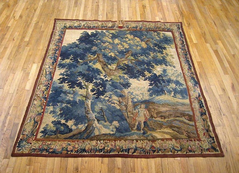 A Flemish Baroque landscape hunting tapestry from the late 17th or early 18th century, depicting a young Archer carrying a bow and arrow within a forest in a meadowland setting. Enclosed within a border of fruiting and flowering elements, with a