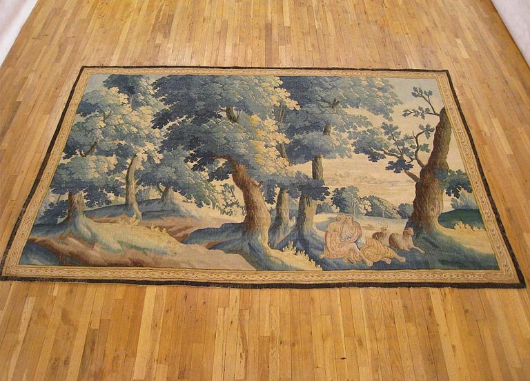 A Flemish pastoral landscape tapestry from the late 17th century, depicting a shepherd and shepherdess reposing in the shade with their sheep at right, within a tranquil wooded landscape, with rolling hills in the distance. Enclosed within a
