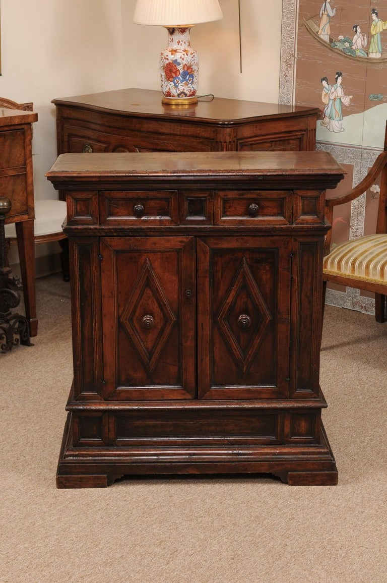 The late 17th century Italian Baroque walnut credenza with narrow rectangular top, 2 paneled drawers and 2 cabinet doors below with lozenge carved panels terminating in plinth base.