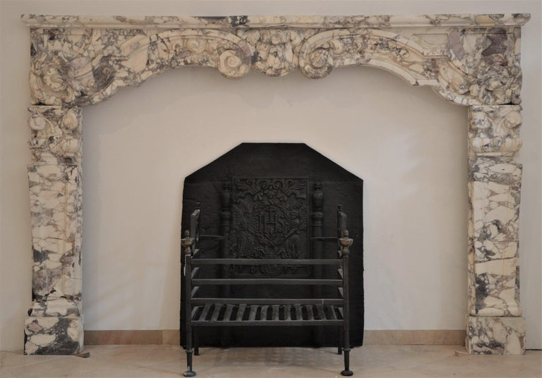 Unique and regal late 17th century Dutch Louis XIV fireplace mantel. This rare and large mantelpiece is executed in the finest Italian breche violet marble.  The boldly carved central keystone is flanked by beautifully scrolled floral decorations