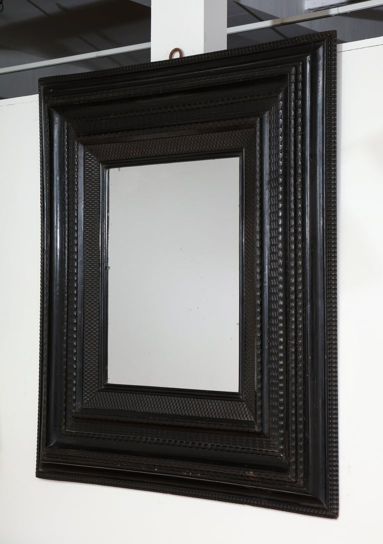 Late 18th C., early 19th C. Italian mirror Ebonized walnut guilloche frame, old silvered glass mirror  Measures: 47 by 41.75 inches.
