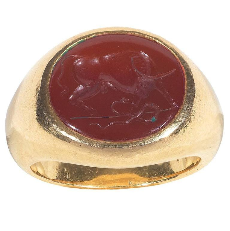 The oval carnelian depicting a standing bull fighting against a snake.  Carnelian size: 15 x 13 mm  Mounted in 18Kt yellow gold chevalier shape ring  Weight: 19.7 gr  Finger size: 8 3/4  In the Christian iconography the bull has been seen as a