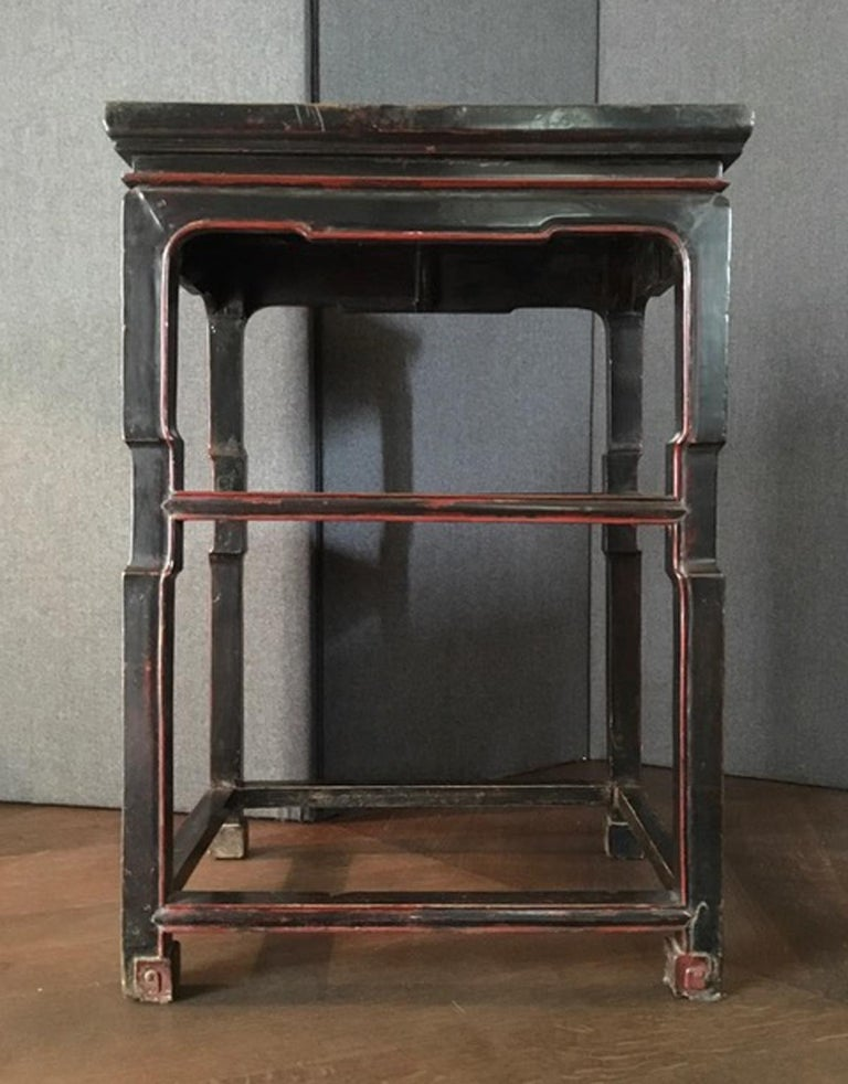 Late 18th century Chinese export lacquered side table in black and red.  This side table has the signs of the time and for this reason it's a piece that has a great charm. The antique black lacquer is not perfect  cause its three Centuries of life,