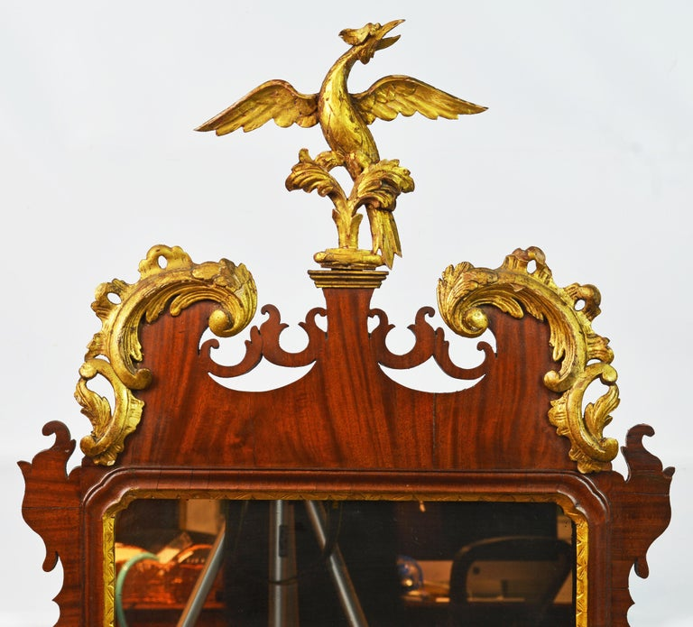 This fine mahogany Chippendale mirror dating to the late 18th century features a pediment with elaborate gilt foliate scrolls centering a carved gilt phoenix bird above sides with carved gilt leaf garlands and a shaped bottom part. We have judged