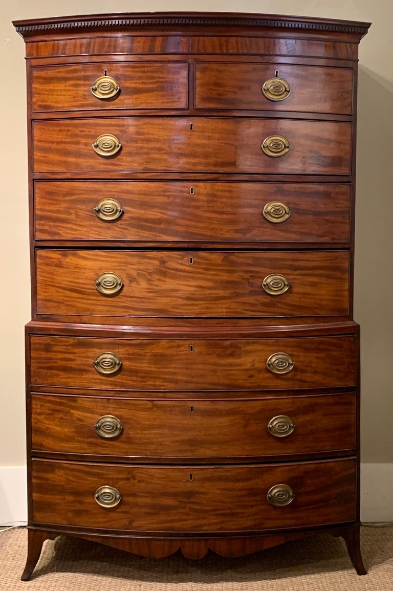 An elegant late 18th century English mahogany bowfront chest on chest. The top portion contains two small drawers over three graduated large drawers and the bottom portion contains three graduated large drawers. The piece is topped with a crown