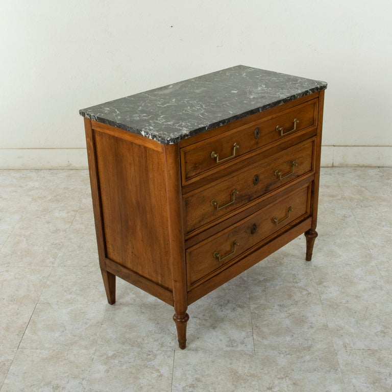 Unusual for its smaller size with a 37.25 inch width, this late 18th century French Louis XVI period commode or chest of drawers features its original Saint Anne marble top. Constructed of solid walnut, this piece has three drawers of dovetail