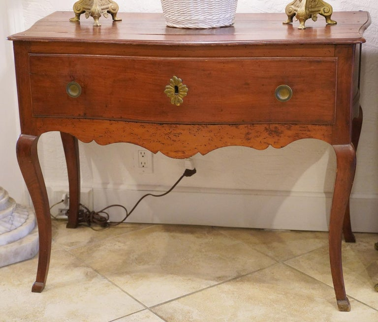 This late 18th century French Provincial cherry serpentine console table features a shaped top above one long serpentine front drawer retaining original hardware and a carved scalloped apron. The table rests on four cabriole legs ending in carved