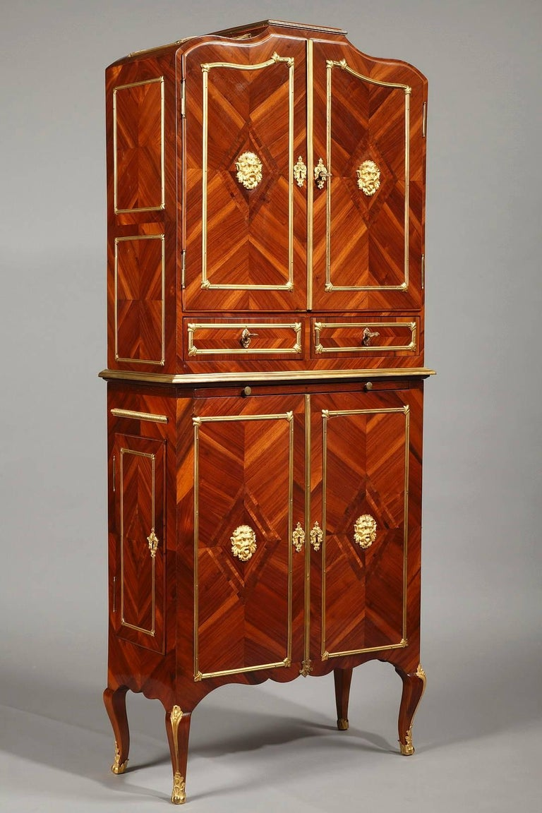 """Late 18th century piece of furniture called a """"cartonnier"""" in wood veneer and used for storing papers. Each section of the piece features a frame of gilt bronze, fluted stripes. Its upper part has two small drawers placed under the two main doors"""