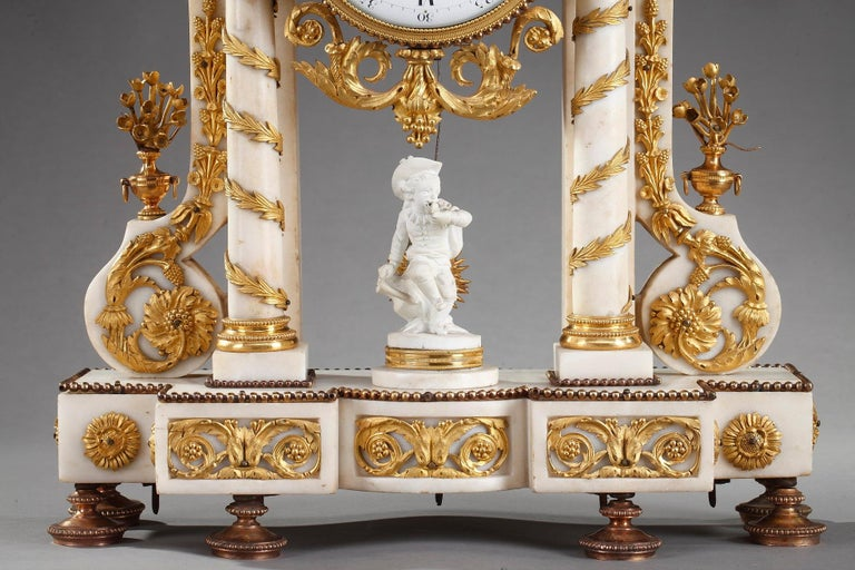 Louis XVI-period portico clock crafted in Carrara marble accentuated by exquisitely detailed ormolu decoration of garlands, flowers, vases, acanthus and laurel leaves. The drum case is supported on a pediment raised on two free standing columns and