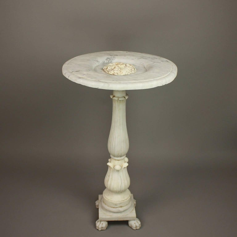 Late 18th century marble fountain carved in Carrara marble and originally the center piece of a larger basin. A circular flat top with a central vine ornament adorns the waterspout. The water would pour over the rim softening the edges of this hard
