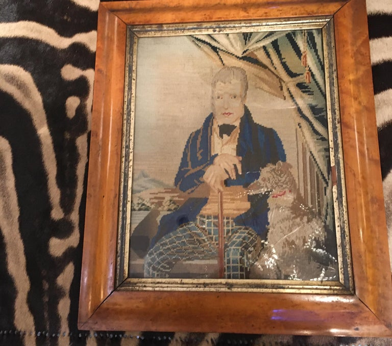 Charming 18th century needlepoint portrait of well dressed gentleman and his dog. wonderful details and colors. Expression and personality are captured by the artist. Framed in gilt and bird's-eye maple.