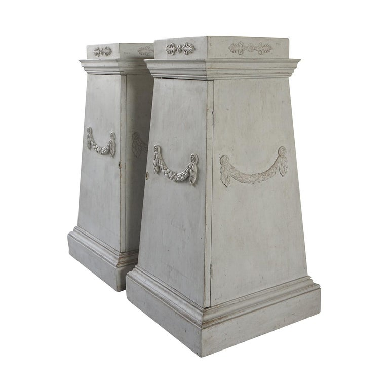 A pair of Gustavian pedestals made of light grey painted pinewood with carved garlands. The hand carved pedestals are in good condition, detailed in the neoclassical Greek style with their original hardware. Wear consistent with age and use, circa