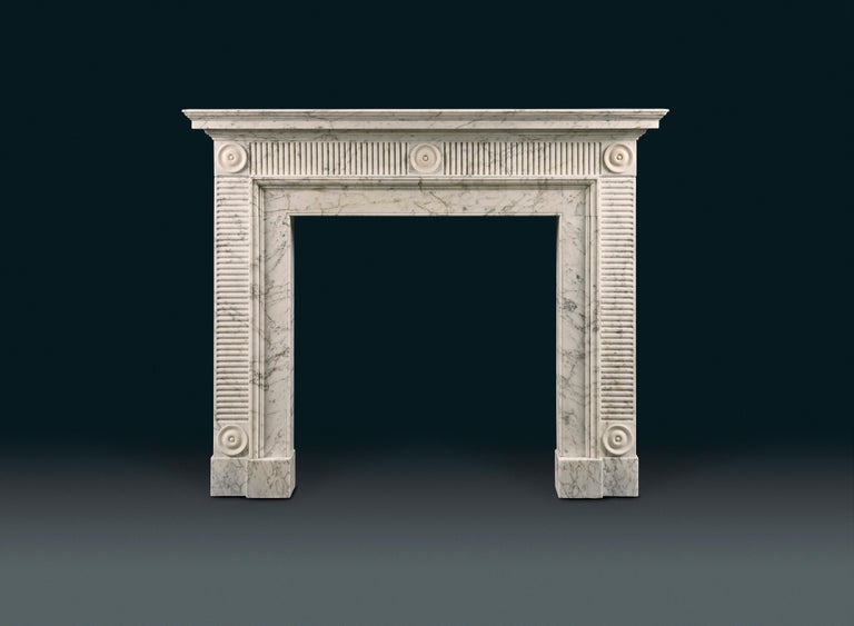 An elegant late 18th century Carrara and white statuary marble chimneypiece in the manner of Sir John Soane. Once installed in the famous Waldorf Astoria Hotel in Manhattan. With a tiered and moulded shelf, the frieze and jambs with horizontal and