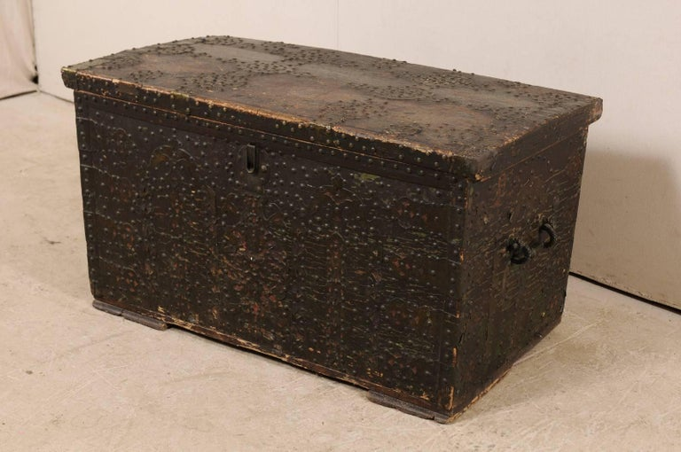 A Spanish Baroque studded coffer from the turn of the 18th and 19th centuries. This antique Spanish coffer, with it's rectangular-shaped body, has been ornately decorated with nailhead brass studs (which have a dark patina from age) along the entire