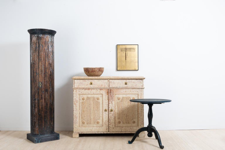 Double doored Gustavian sideboard with dry scarped to original paint. The doors are decorated with panels of fluted decor and carved circles. The lock and key are original and in fully functional condition. Manufactured in the middle of Sweden,