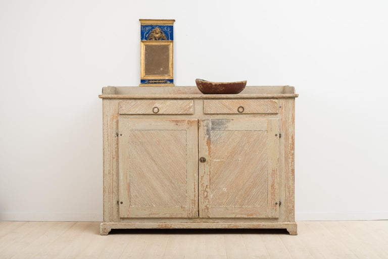Gustavian sideboard from northern Sweden that's been dry scraped to original paint. Originates from an old farmhouse located in a small village called Stöde in northern Sweden. It is rare to find sideboards this long and low. Working lock and key,