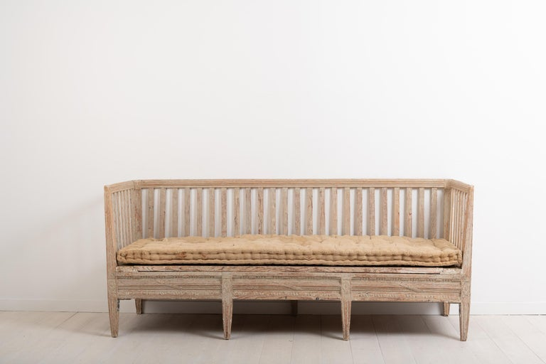 Antique sofa bench from the late 18th century. The bench is neoclassic and made in Sweden circa 1770. It is decorated with carved wooden decorations typical for the neoclassic period. Original and distressed paint from the 1770s. Natural patina. One