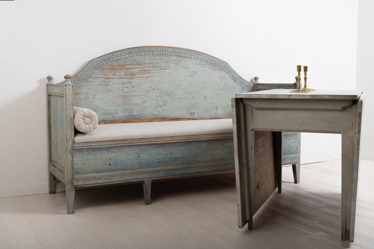 Late 18th century unusual Gustavian sofa from northern Sweden. The sofa has a straight model with a curved back and decorations carved to look like leafs. Good patina. Dry scarped to the original blue paint. The seat is later, likely from the 1800s