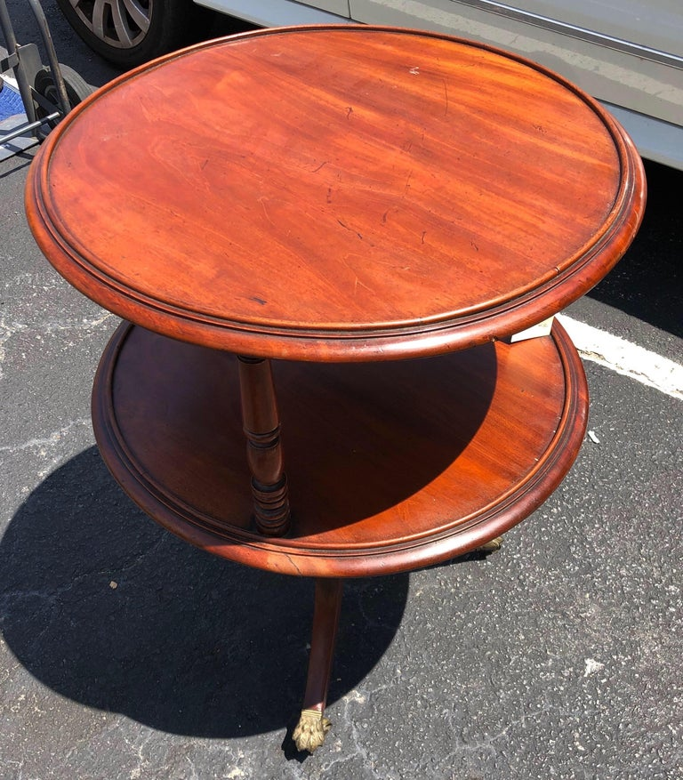 Late 18th-early 19th century Georgian mahogany two tier dumbwaiter with molded shelves, turned supports, sabre legs resting on original brass paw feet castors.  Great color and patina all around. Nice size- height is good for a side table.