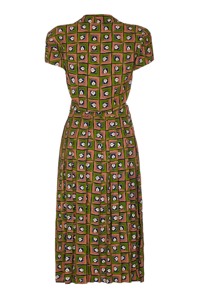 Fabulous Suzy Perette labelled dress with novelty leaf print in navy, green and ochre.  The company was founded during the 1940s and headquartered in New York.  The owner had a licence to copy elements of Christian Dior's designs but they were much
