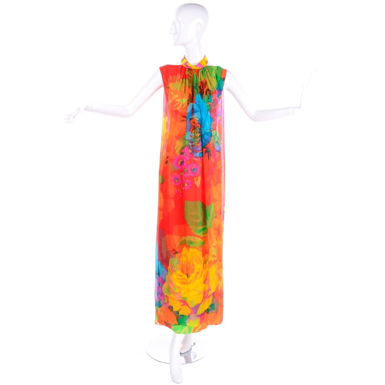 This vintage dress is a beautiful example of the talent of Japanese designer Hanae Mori! The fabric is printed with bold oversized flowers, as was Mori's signature, in shades of red, orange, green, yellow, purple and pink. The silk chiffon printed