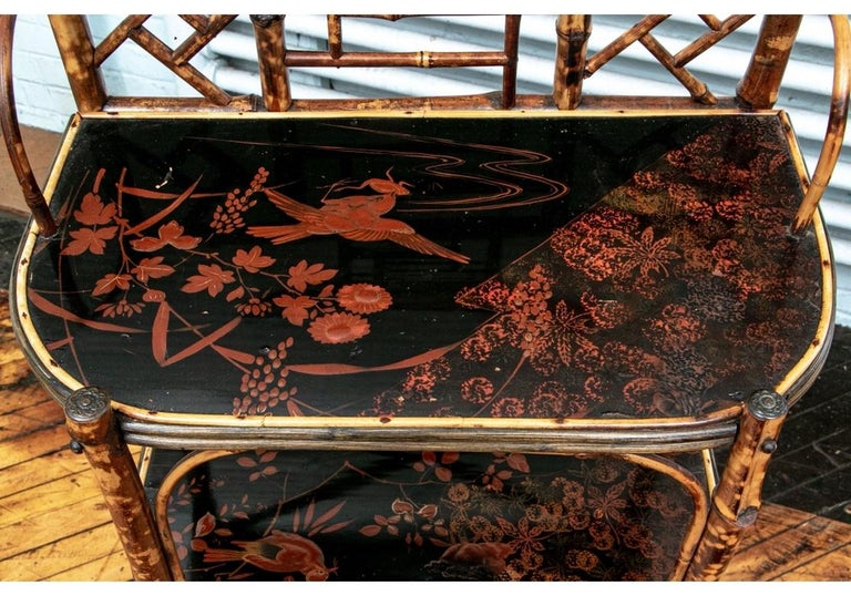 A fine antique étagère with good proportions and condition. The Chinese Chippendale form holds three painted and lacquered shelves which portray birds, branches, leaves and a little frog. All of the painting is executed in a Cinnebar shade against a