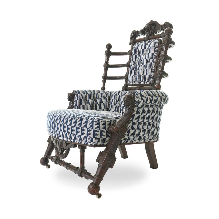 Carved Renaissance Revival walnut armchairattributed to George Hunzinger (1835-1898), featuring multiple detailed maiden's head carvings, turned spindles, and a partially upholstered back with curved sides. Dating back to the late 19th century, all