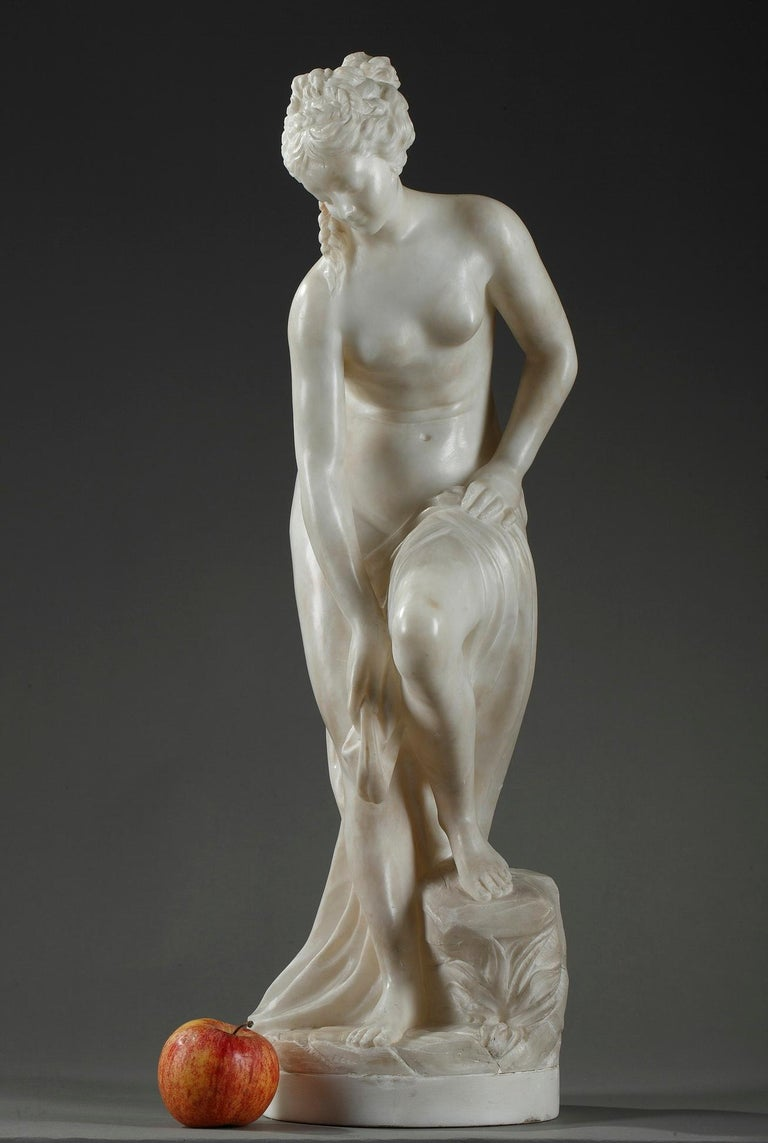 Alabaster statue featuring a nude bather removing the drape around her hips while advancing toward the river. Her light contraposto pose accentuates her feminine curves. Carved of alabaster, the sculpture exhibits neoclassical grace. This enchanting