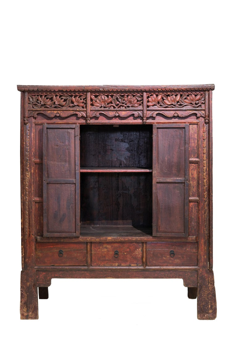 A late 19th century red lacquered cabinet from Shanxi province, China. Heavy floral carving in front, some of the original color on the flowers are still visible. Iron door handles and hinges. Original red color and patina with a clear matte lacquer