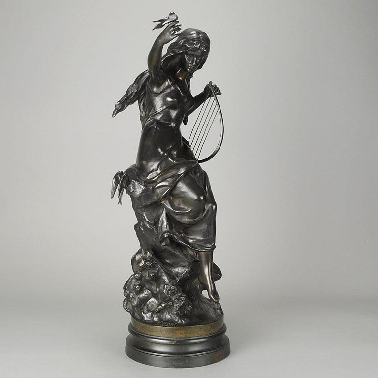 A very fine late 19th century bronze study of an Art Nouveau beauty seated upon a rocky outcrop with a harp in one hand and the other raised above her head with a small bird perched on it, the bronze with excellent hand finished detail and rich