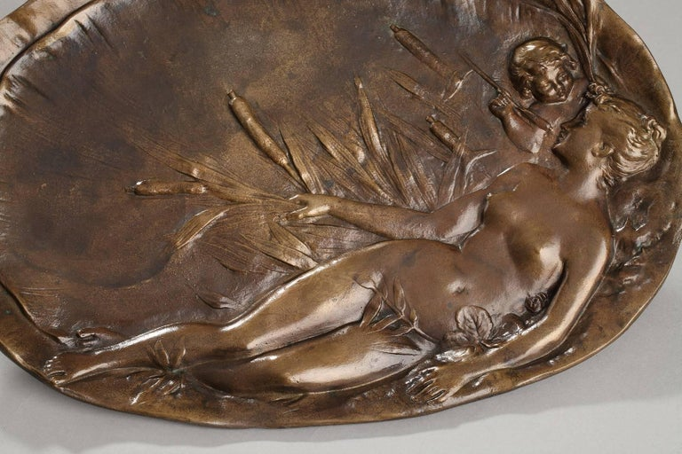 Oval platter in patinated bronze decorated with a sculpted, bas-relief woman stretched out among reeds and cattails. She is nude, and behind her, a young cupid is gazing at her face her through the reeds. This scene, saturated with the sensuality of