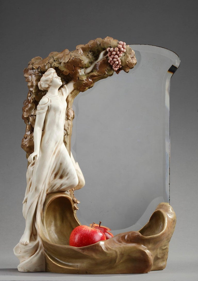 This original Art Nouveau mirror was crafted of polychrome porcelain. The beleved, rectangular glass is decorated with a young woman picking a grape. The lower part of the mirror forms a receptacle. Marked underneath: Royal Dux Bohemia and numbered