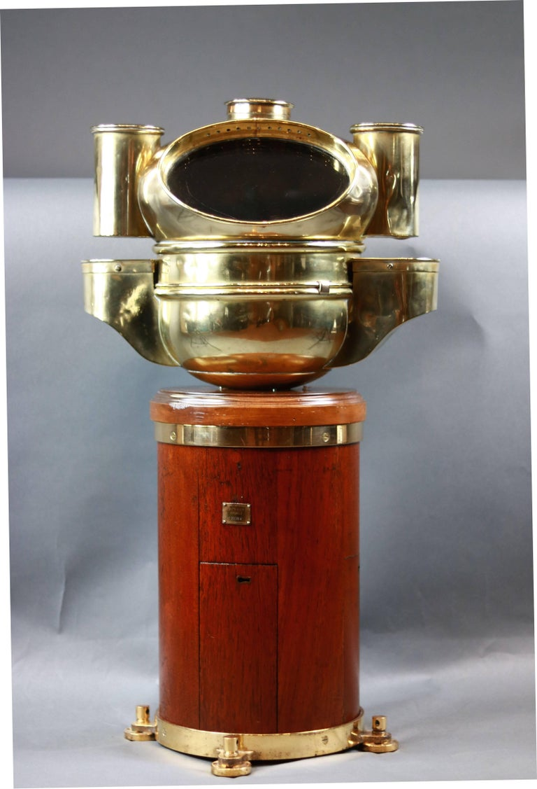 English yacht binnacle by Pascall Atkey of Cowes. Round, varnished mahogany base with brass feet. Hood is solid brass with side burner housing. Compass inside reads