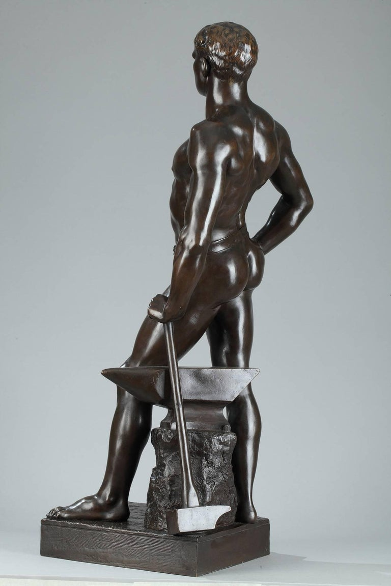 Bronze sculpture with brown patina featuring a blacksmith standing while leaning against his anvil and hammer. He is presented nude, standing in contrapposto, his left leg forward and slightly bent and set on a square base. The title sculpted on the