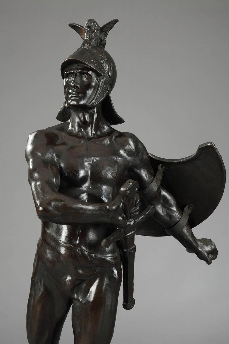 Large patinated bronze figure of an Antiquity warrior. He is set on a base decorated with battle scenes, marked: Les Chasseurs Éclaireurs de Bruxelles à leur Lt Colonel O. Tahon 1870-1910 (The Hunters Scouts from Brussels to their Lt Colonel O.