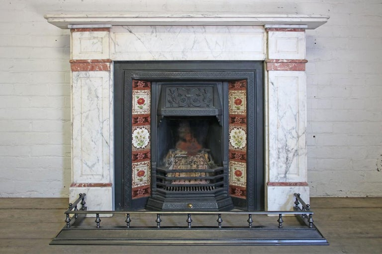 Late 19th century Carrara marble fireplace surround with rouge marble interruptions, circa 1880.   This surround is currently awaiting restoration, please enquire as to the lead time before placing an order. The price listed is once the fireplace