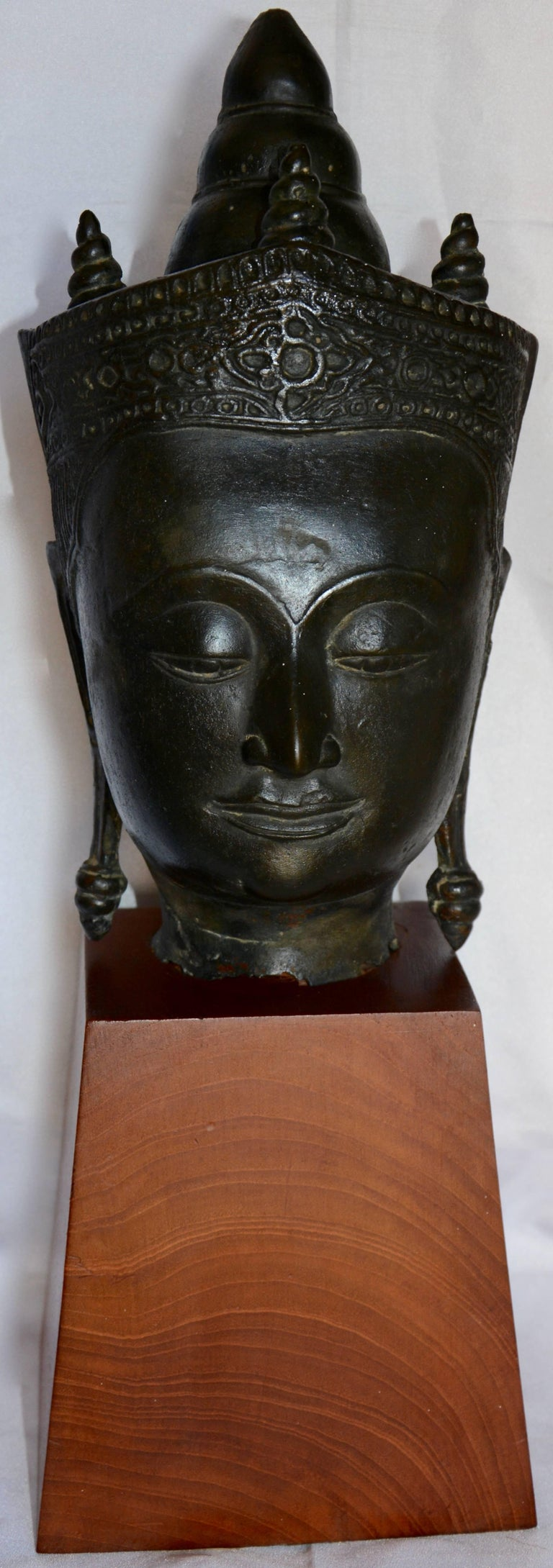 Featured is a fabulous cast bronze Thai Buddha bust statue mounted on a wooden base. It has the features of a traditionally designed Buddha statue, including stylized crown and elongated earlobes. The bronze head is hollow, and the neck fits over a