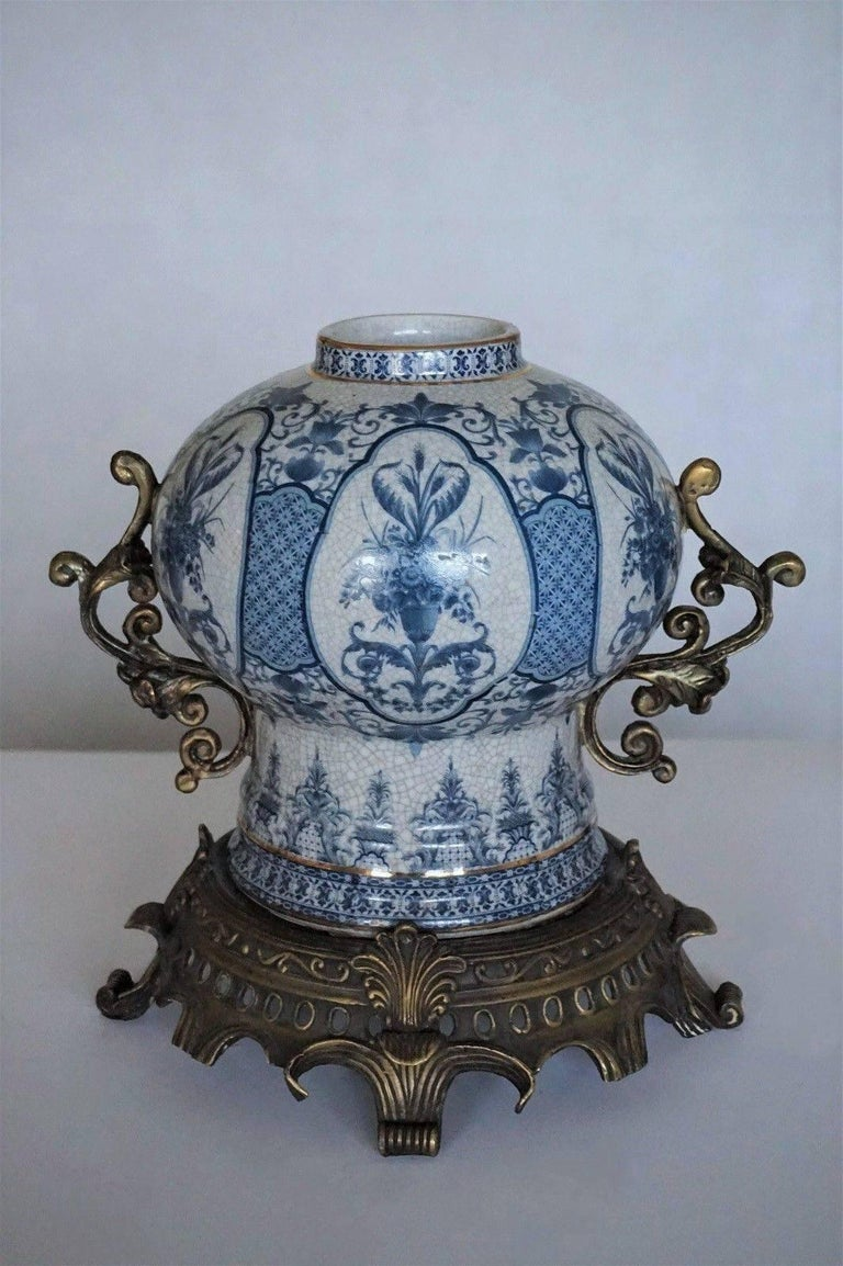 Transfer decorated Chinoiserie blue and white porcelain globular jar with bronze handles and stand, late 19th century. White porcelain hand painted in brilliant blue with floral panels and glazed. Measures: Height including bronze stand 12 in (30