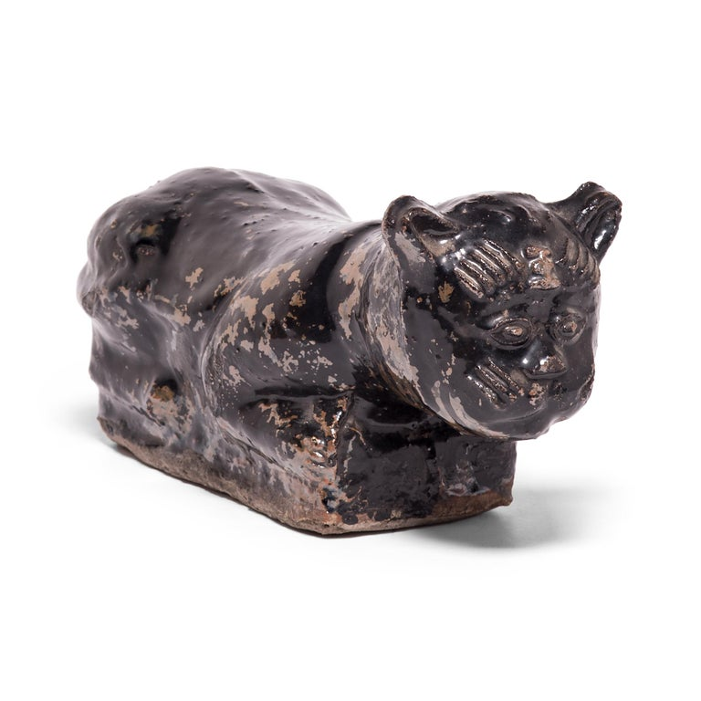 To keep her elaborate hairstyle intact while sleeping, a well-to-do Qing-dynasty woman once used this ceramic headrest as a pillow. The headrest is shaped as a crouching house cat, cloaked in a beautifully irregular dark brown glaze. Drawn upon its