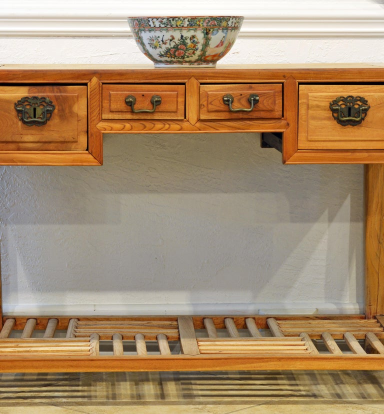 This late 19th century Chinese natural color elm wood desk features two center small drawers flanked by two deeper drawers. The legs are joined by a low lattice shelf in a traditional Chinese pattern.