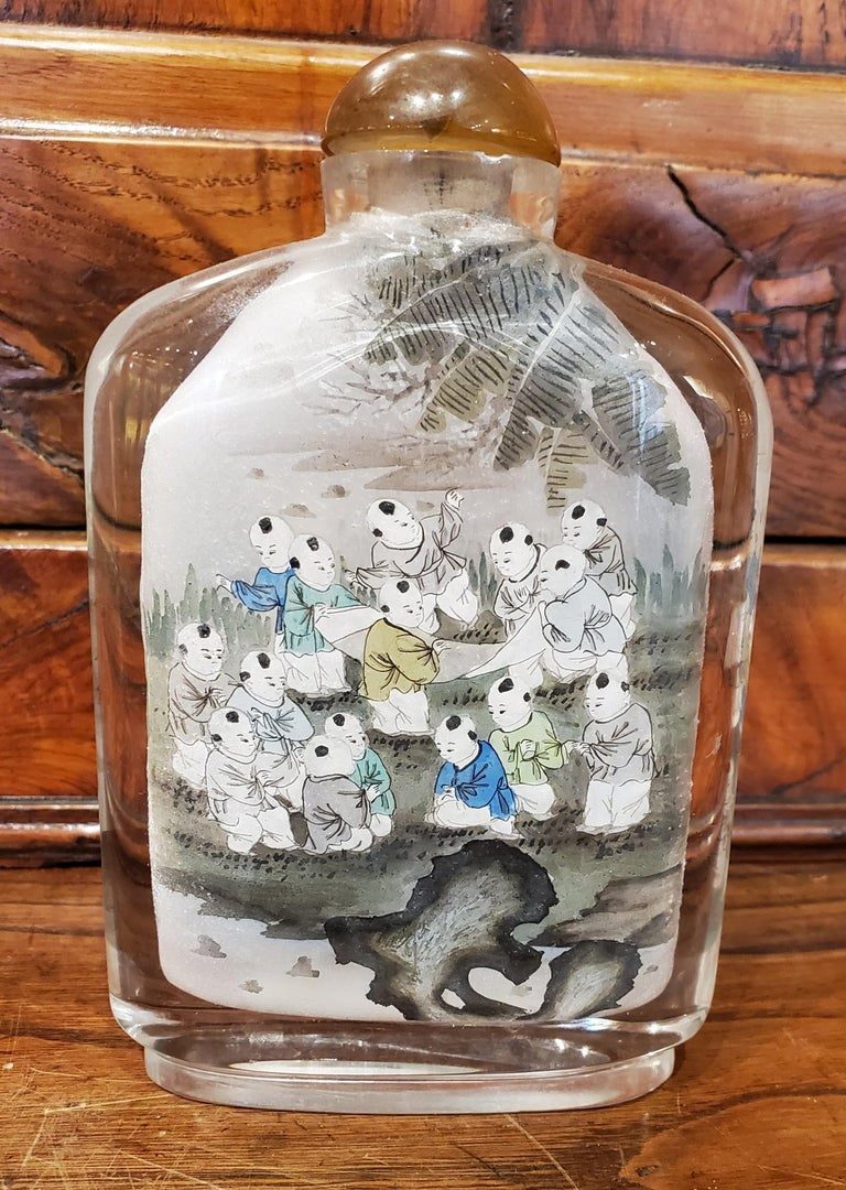 This beautiful late 19th century Chinese reverse painted glass snuff bottle is an incredible example of the intricate skill required for reverse painting with a detailed scene inside the front and back surfaces. This painting technique is known as