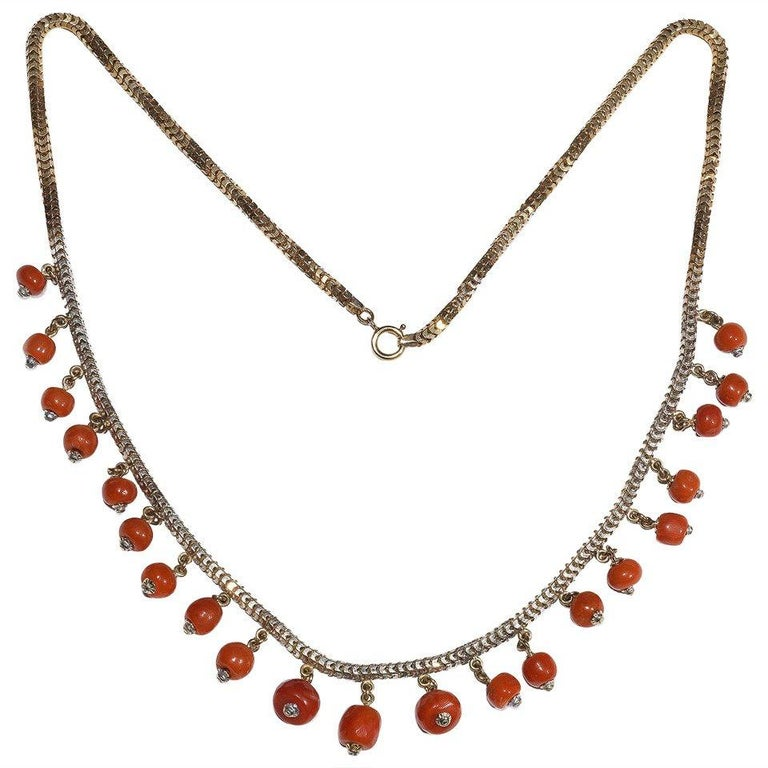 A snake-link chain suspends a fringe of coral corallium rubrum beads, length 40.5cm