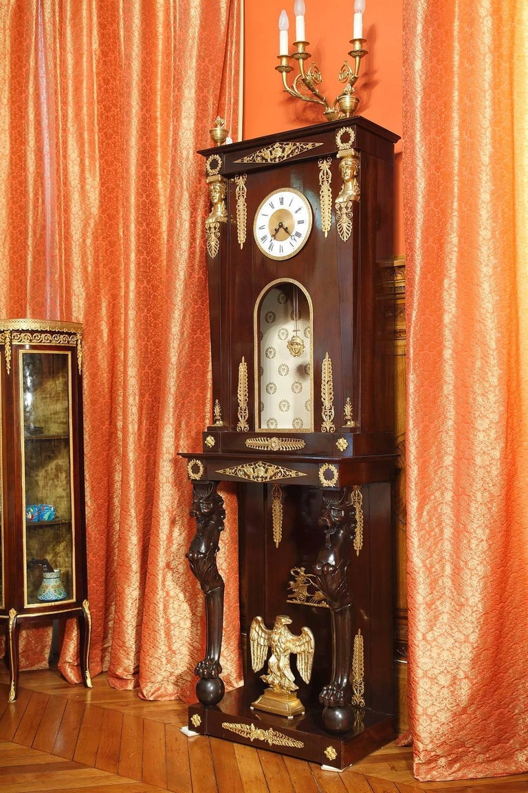 Impressive mahogany longcase clock with gilt and sculpted decorative bronze elements such as fantastic animals, diamond-shaped patterns, scrollwork, and foliage. This floor clock is composed of two parts: the upper part which contains the white
